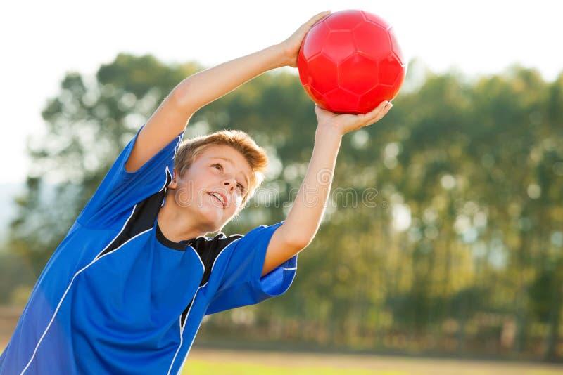 Muchacho joven que coge la bola roja al aire libre. imágenes de archivo libres de regalías