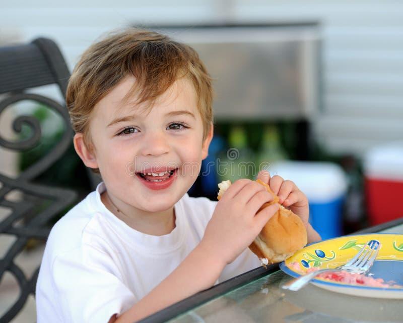 Muchacho joven que come el perrito caliente foto de archivo libre de regalías