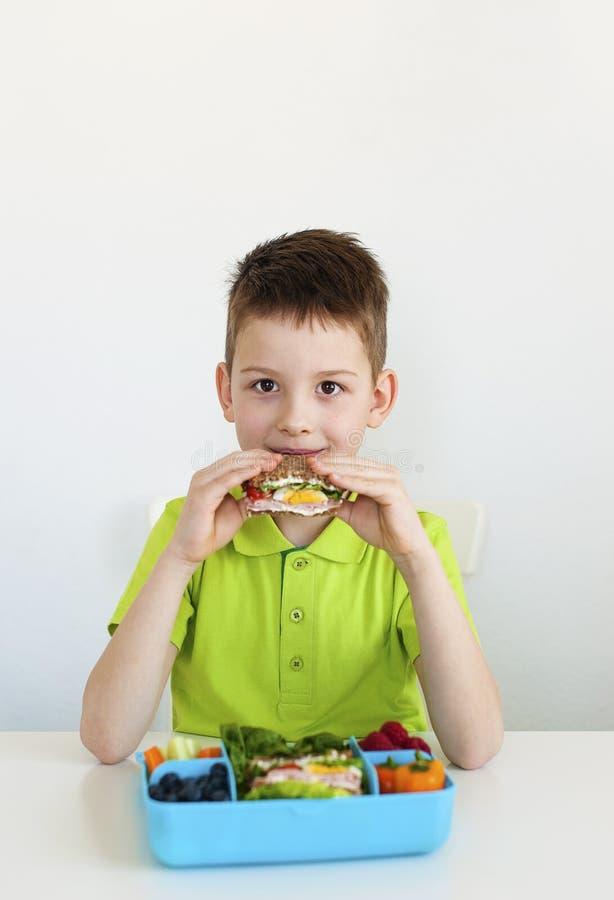 Muchacho joven que come la comida sana imagen de archivo