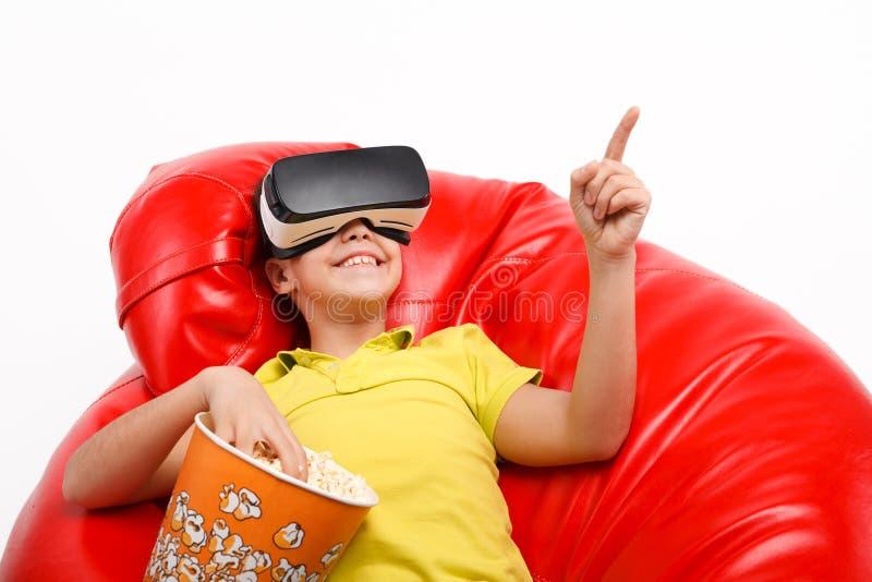 Muchacho joven que come las palomitas y que usa las auriculares de VR imagenes de archivo
