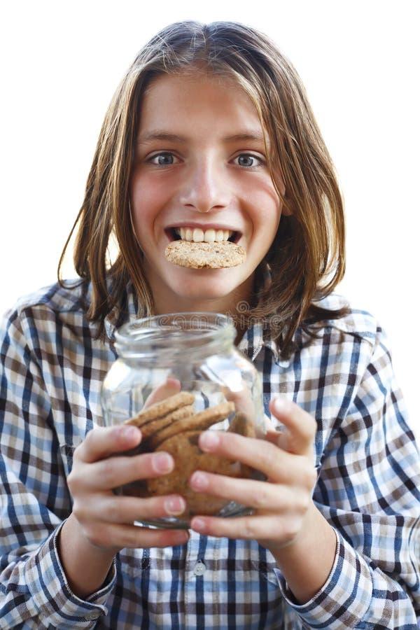 Muchacho joven que come una galleta fotografía de archivo