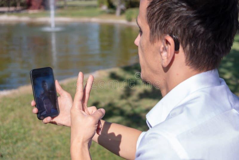 Muchacho joven que comunica con lenguaje de signos en el teléfono elegante imágenes de archivo libres de regalías