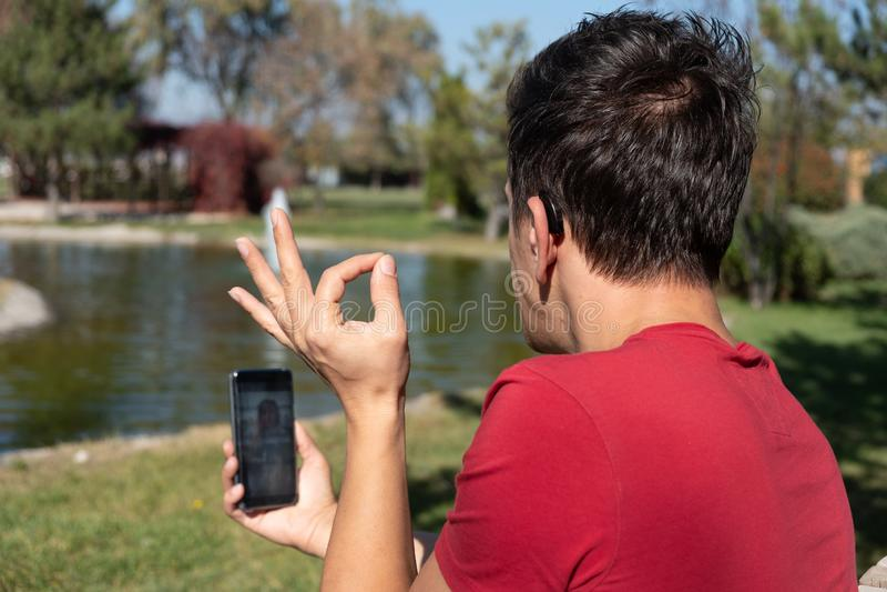 Muchacho joven que comunica con lenguaje de signos en el teléfono elegante fotos de archivo
