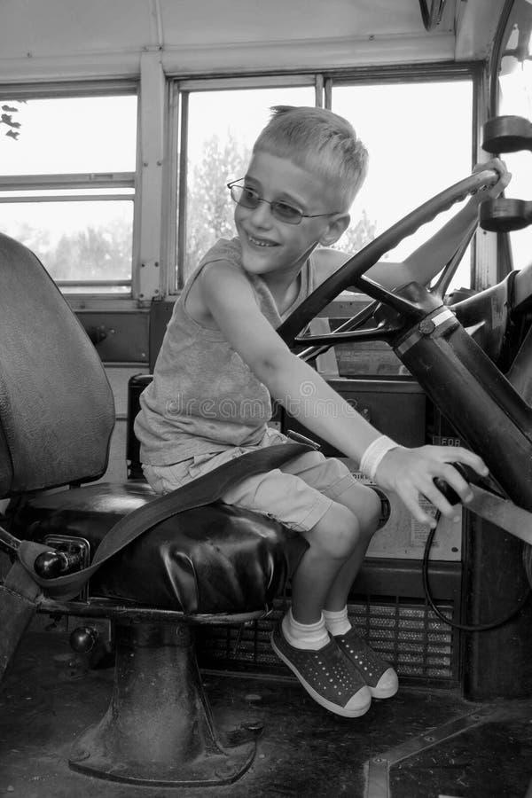 Muchacho joven que conduce el autobús escolar antiguo foto de archivo libre de regalías