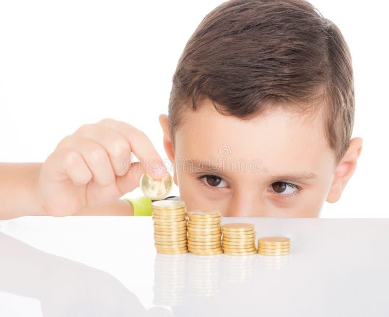 Muchacho joven que cuenta sus monedas imagenes de archivo