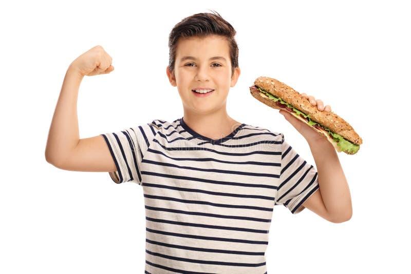 Muchacho joven que dobla su bíceps y que sostiene un bocadillo foto de archivo libre de regalías