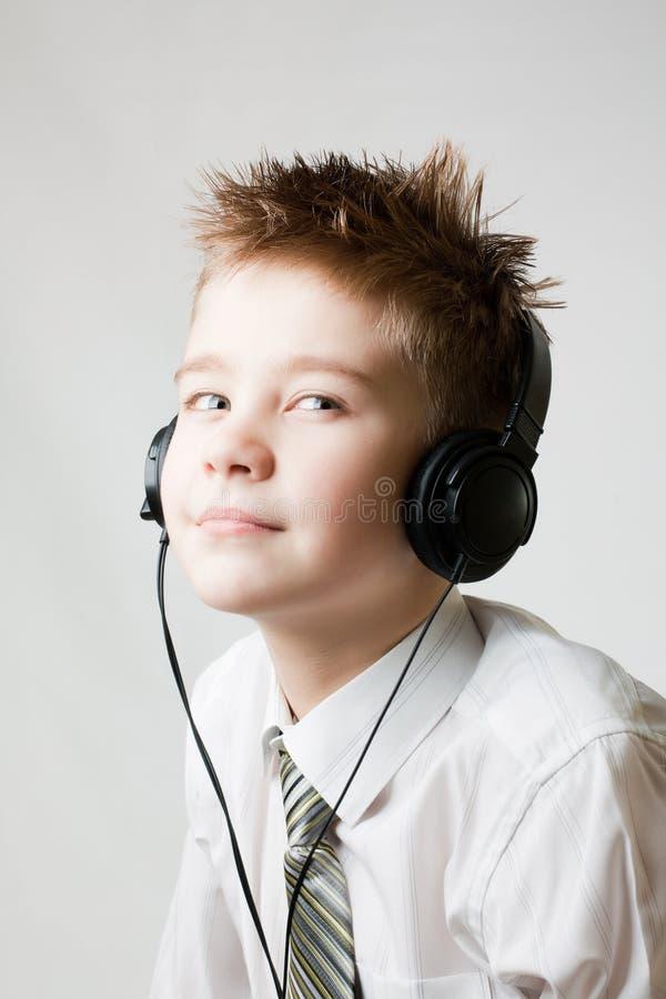 Muchacho joven que escucha los teléfonos principales foto de archivo libre de regalías