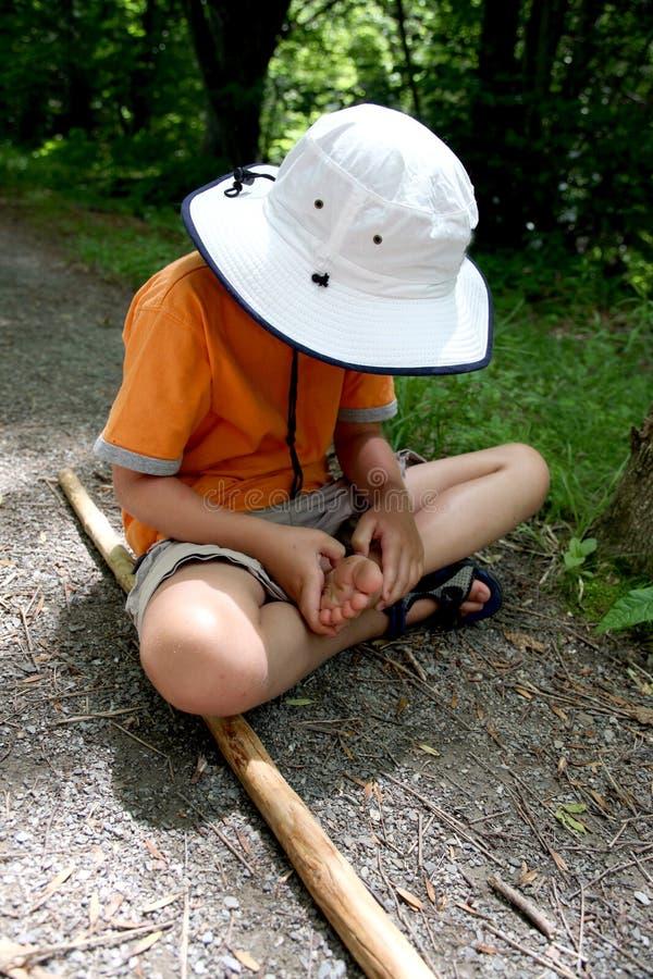 Muchacho joven que examina su pie fotos de archivo