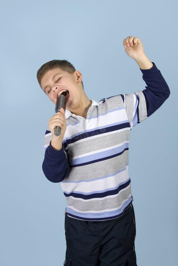 Muchacho joven que finge a la estrella del rock imagen de archivo libre de regalías