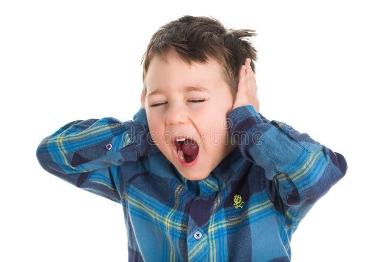 Muchacho joven que grita y que cubre los oídos foto de archivo libre de regalías
