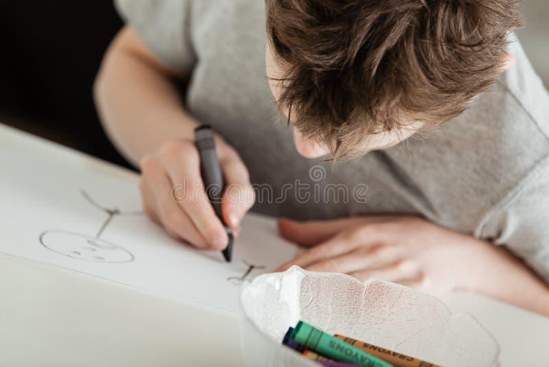 Muchacho joven que hace las ilustraciones usando los creyones en la tabla fotografía de archivo