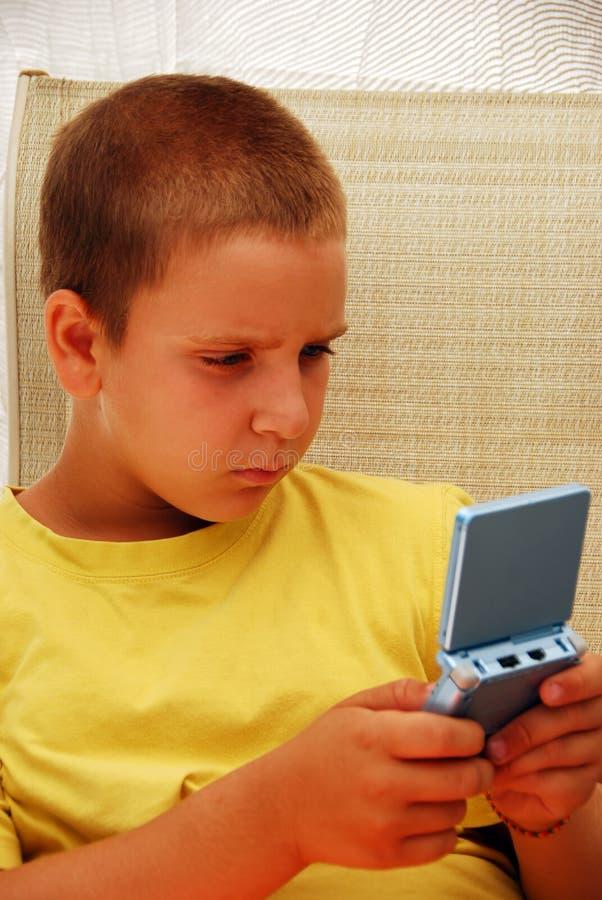 Muchacho joven que juega al juego video imagen de archivo