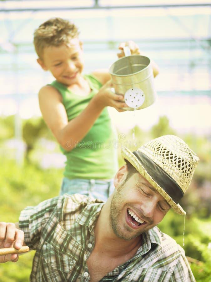 Muchacho joven que juega con su padre en una casa verde fotos de archivo