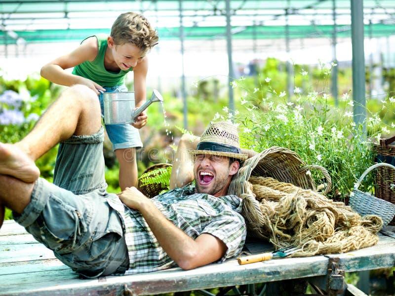 Muchacho joven que juega con su padre en una casa verde imagenes de archivo