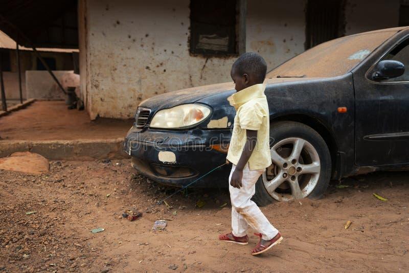 Muchacho joven que juega con un coche hecho a sí mismo del juguete en la vecindad de Missira en la ciudad de Bissau, Guinea-Bissa imagenes de archivo