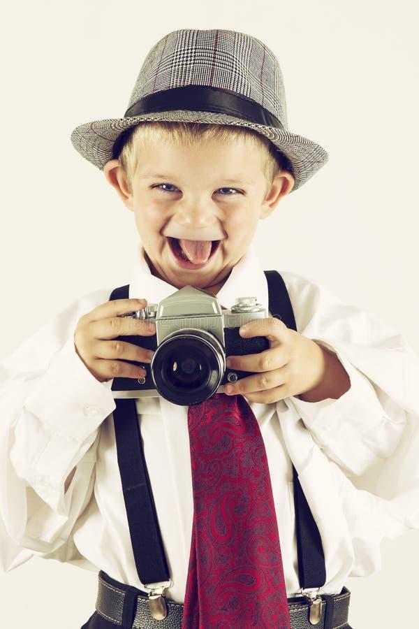 Muchacho joven que juega con una cámara vieja para ser fotógrafo imagen de archivo libre de regalías