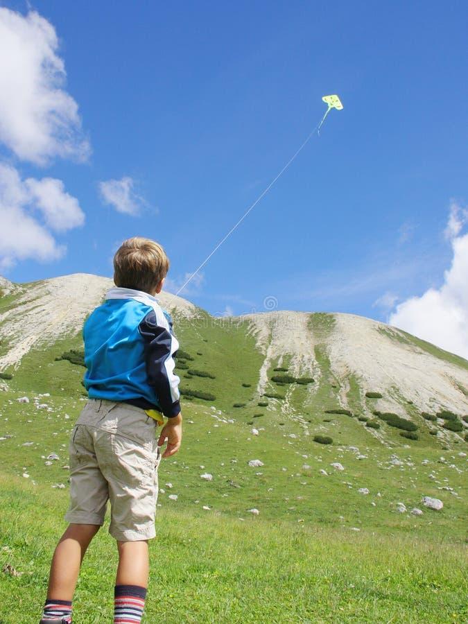 Muchacho joven que juega con una cometa amarilla fotos de archivo