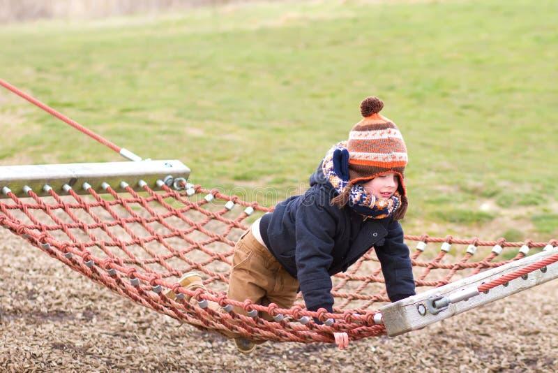 muchacho joven que juega en el parque en un día frío imagenes de archivo