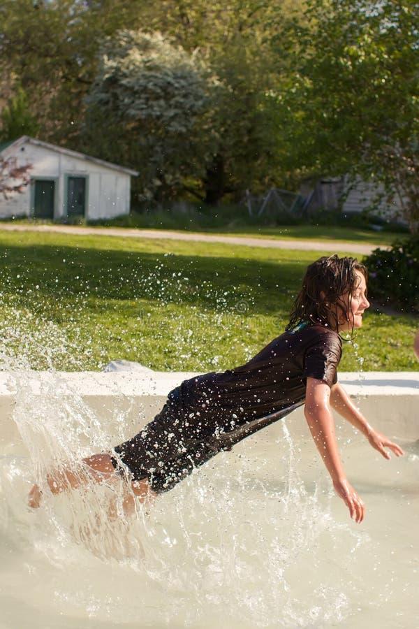 Muchacho joven que juega en piscina fotografía de archivo libre de regalías