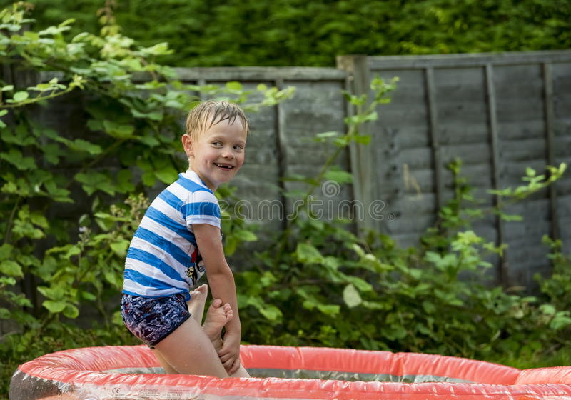 Muchacho joven que juega en una piscina inflable fotos de archivo