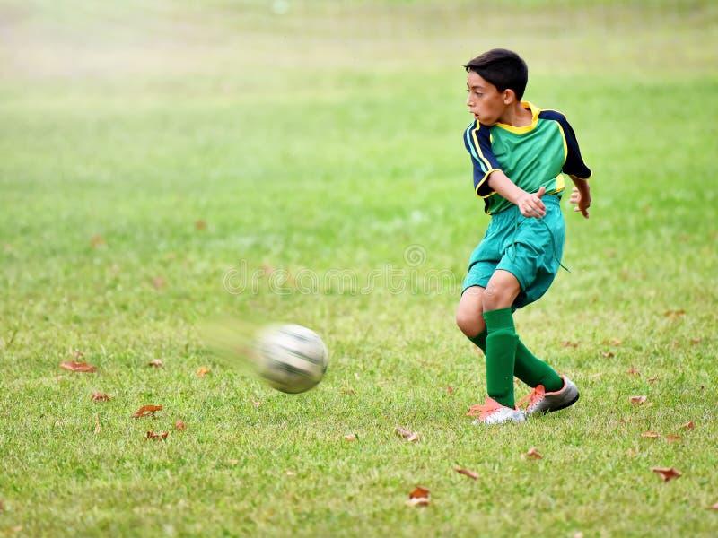 Muchacho joven que juega a fútbol foto de archivo