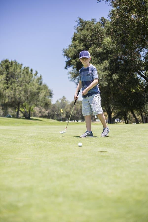 Muchacho joven que juega a golf fotos de archivo libres de regalías