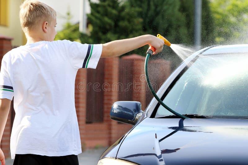 Muchacho joven que lava el coche con la manguera imagen de archivo libre de regalías