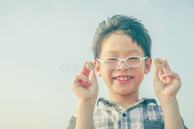 Muchacho joven que lleva a cabo la cáscara sobre fondo del cielo fotos de archivo