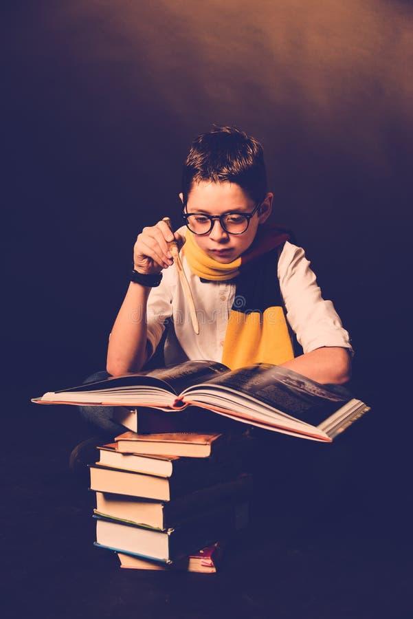 Muchacho joven que lleva una bufanda rojo-amarilla y los libros de lectura de los vidrios en un fondo negro Concepto de imaginaci imagen de archivo