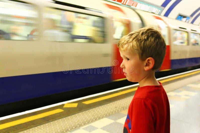 Muchacho joven que mira el tren subterráneo fotos de archivo