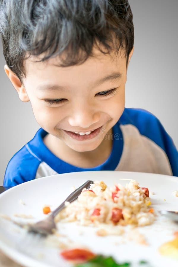 Muchacho joven que mira la comida emocionado en casa fotografía de archivo libre de regalías