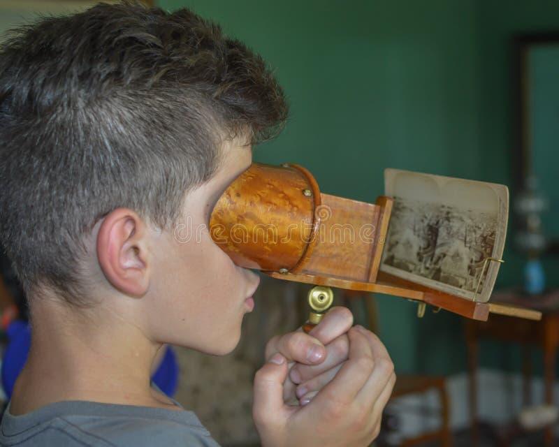 Muchacho joven que mira la fotografía vieja imagen de archivo