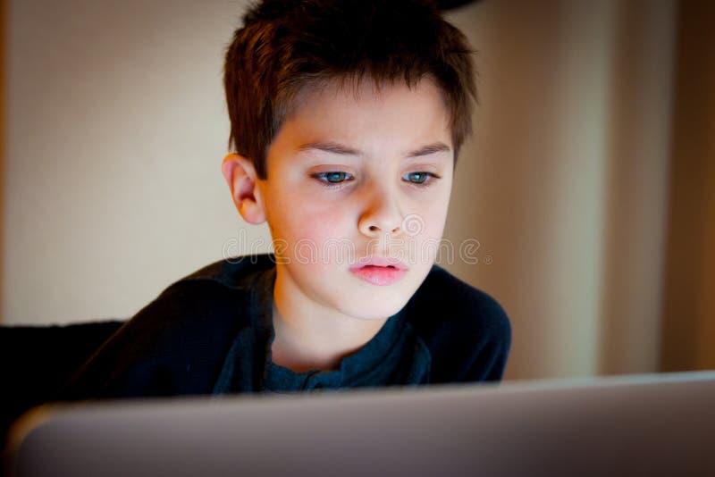 Muchacho joven que mira la pantalla de ordenador fotografía de archivo