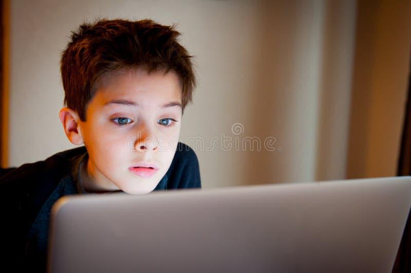 Muchacho joven que mira la pantalla de ordenador fotos de archivo