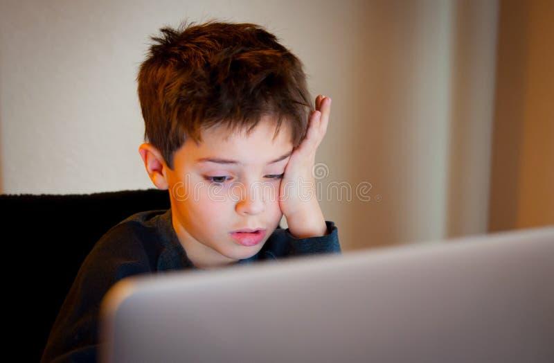 Muchacho joven que mira la pantalla de ordenador imagenes de archivo