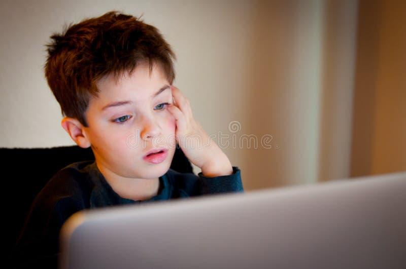 Muchacho joven que mira la pantalla de ordenador fotografía de archivo libre de regalías