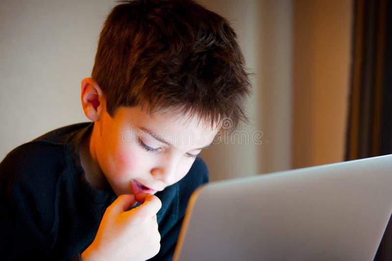 Muchacho joven que mira la pantalla de ordenador foto de archivo