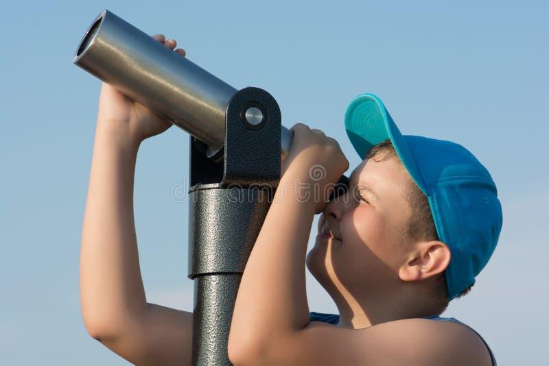 Muchacho joven que mira a través de un telescopio imagen de archivo libre de regalías