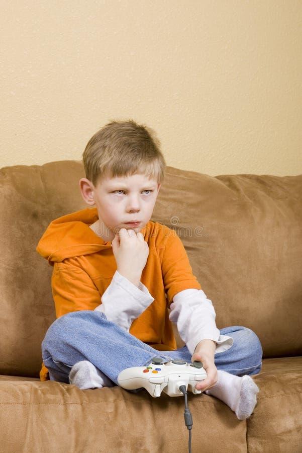 Muchacho joven que pierde en el videojuego imagenes de archivo