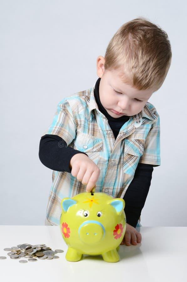 Muchacho joven que pone sus ahorros a una hucha imagen de archivo