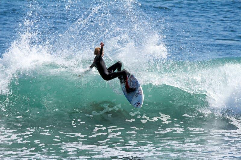 Muchacho joven que practica surf una onda en California foto de archivo libre de regalías