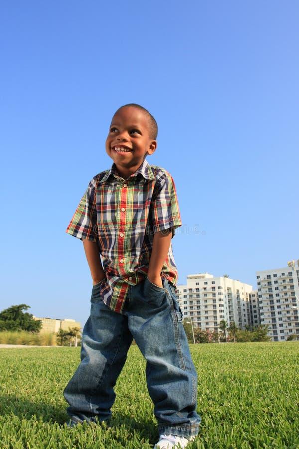 Muchacho joven que presenta en la hierba fotos de archivo