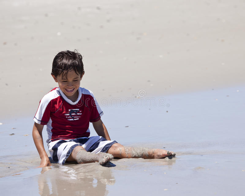 Muchacho joven que ríe como él juega en arena en la playa fotografía de archivo