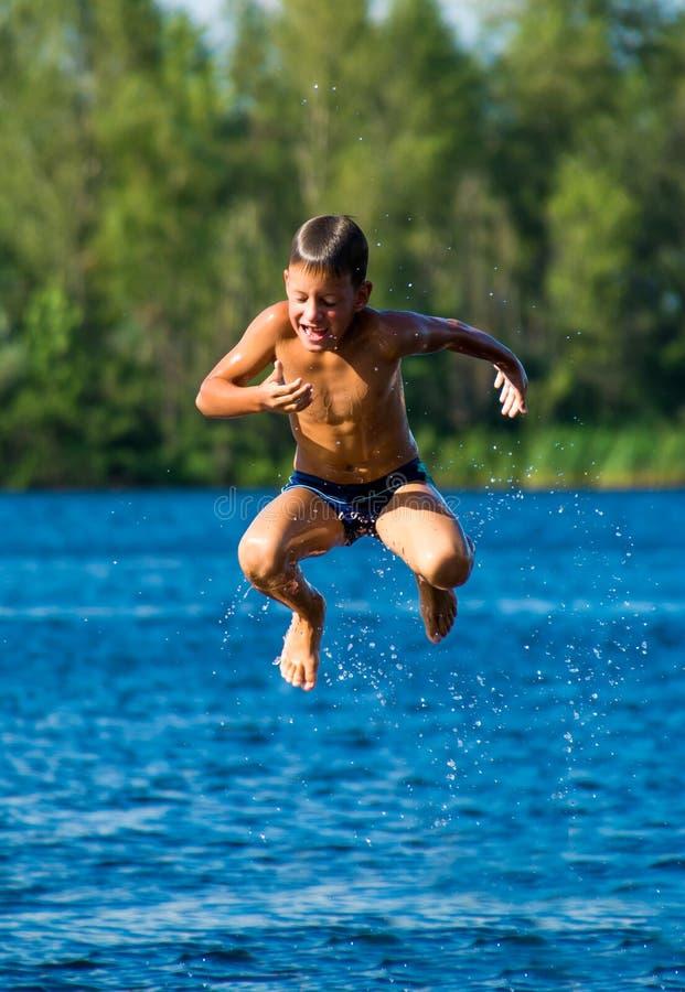 Muchacho joven que salta en el agua foto de archivo