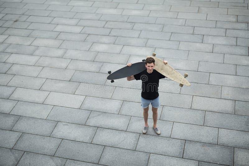 Muchacho joven que se coloca con diverso longboard dos fotografía de archivo libre de regalías