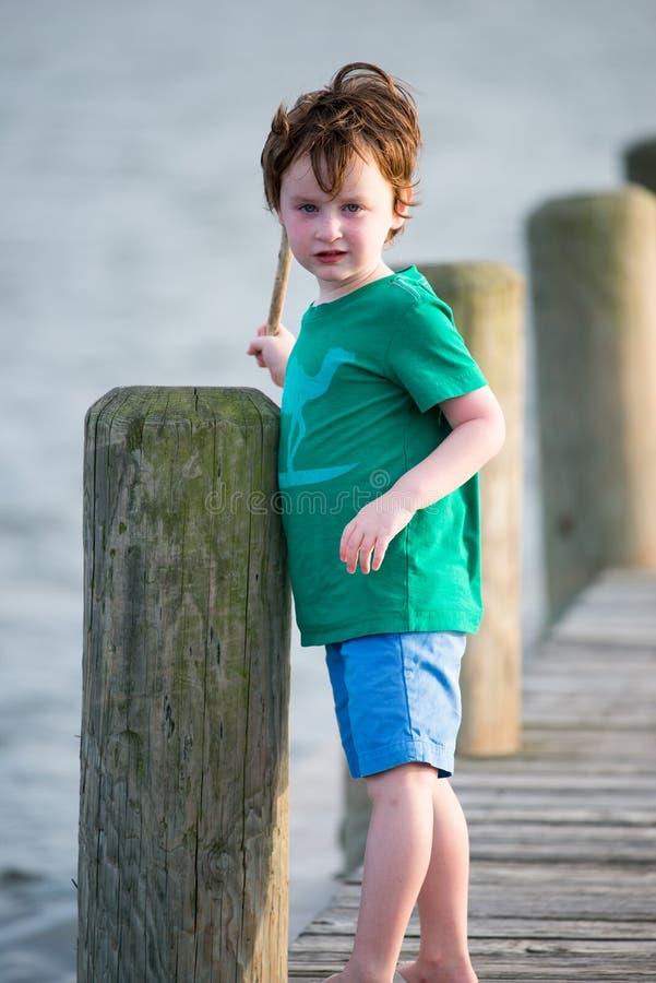 Muchacho joven que se coloca en un muelle rústico de madera que sostiene un palillo en un día de verano caliente fotos de archivo libres de regalías