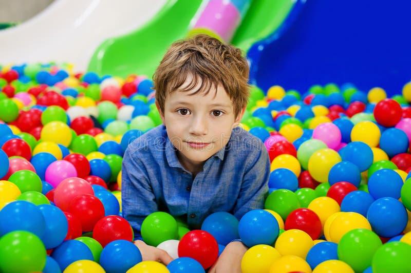 Muchacho joven que se divierte que juega con las bolas plásticas coloridas imagen de archivo libre de regalías