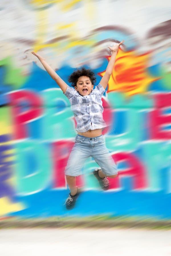 Muchacho joven que se divierte que salta en el aire imagen de archivo