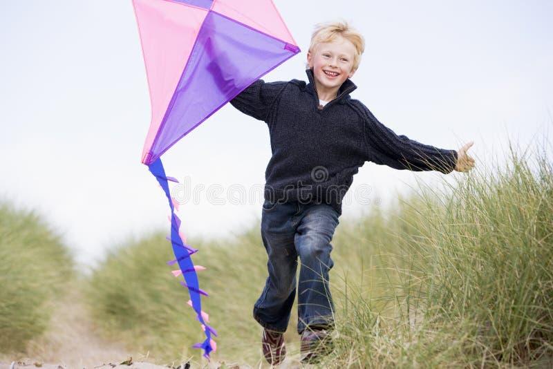 Muchacho joven que se ejecuta en la playa con la sonrisa de la cometa imagen de archivo