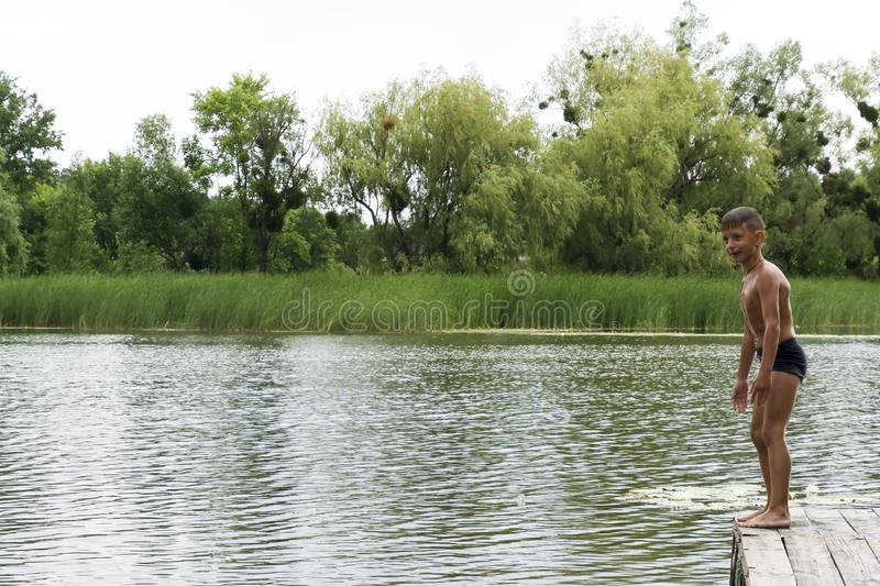 Muchacho joven que se prepara al salto en el lago, diversión del verano imagen de archivo